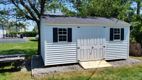 10x16 gable white vinyl siding, double 30 inch 6-panel doors, 2 windows, black shutters, black roof, 60 inch ramp