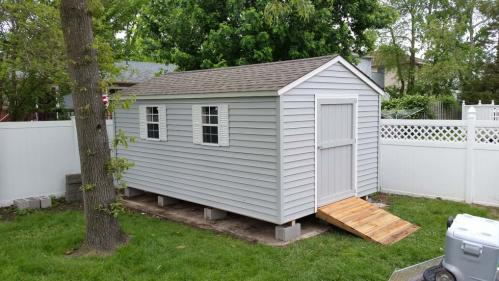 10x16 tackroom gray vinyl siding, 48 inch door, 2 windows, white shutters, weathered wood roof, custom ramp